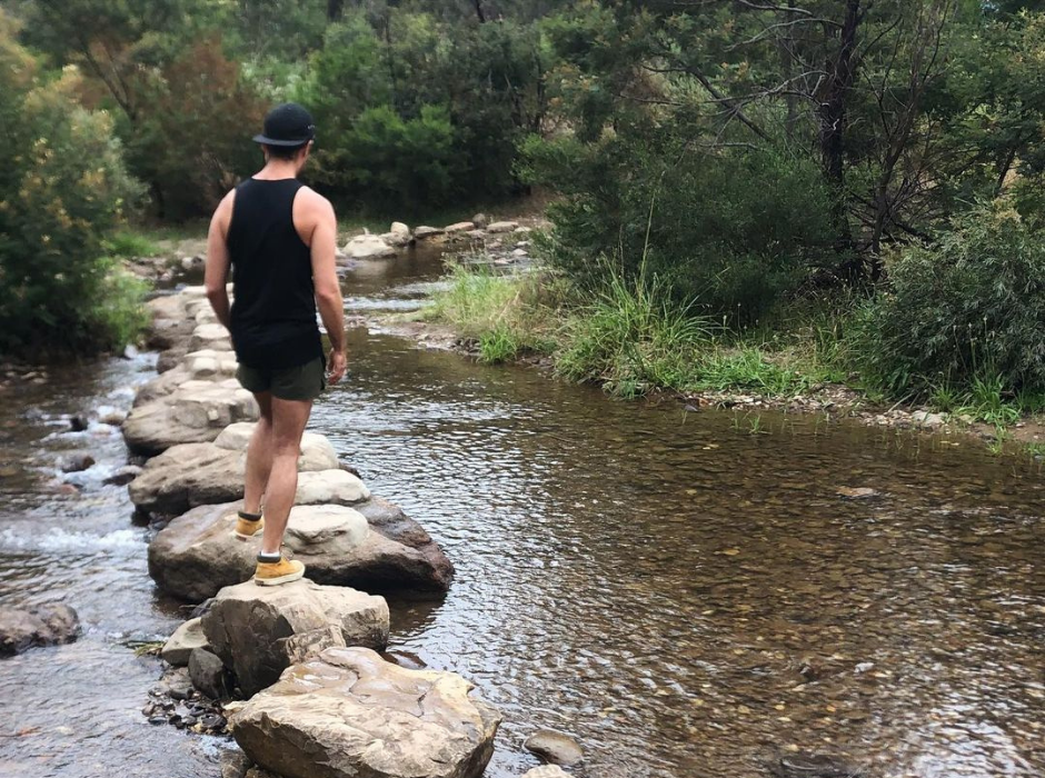 A photo of Dov from behind standing on rocks above a stream of water