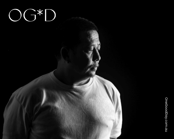 A man wearing a white t-shirt looking to the side. The background is black and the left side of him is covered in shadow..